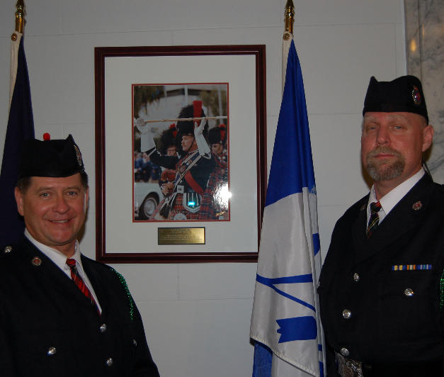 Two band members beside photo of Drum Major P.J. Bawn at Butte - Silverbow Courthouse