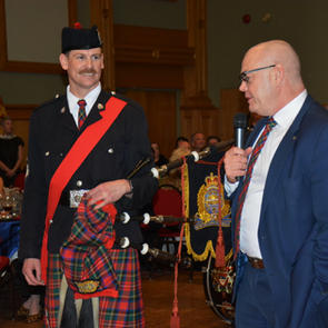 Chief McFee congratulating the new Pipe Major Dale McDonald