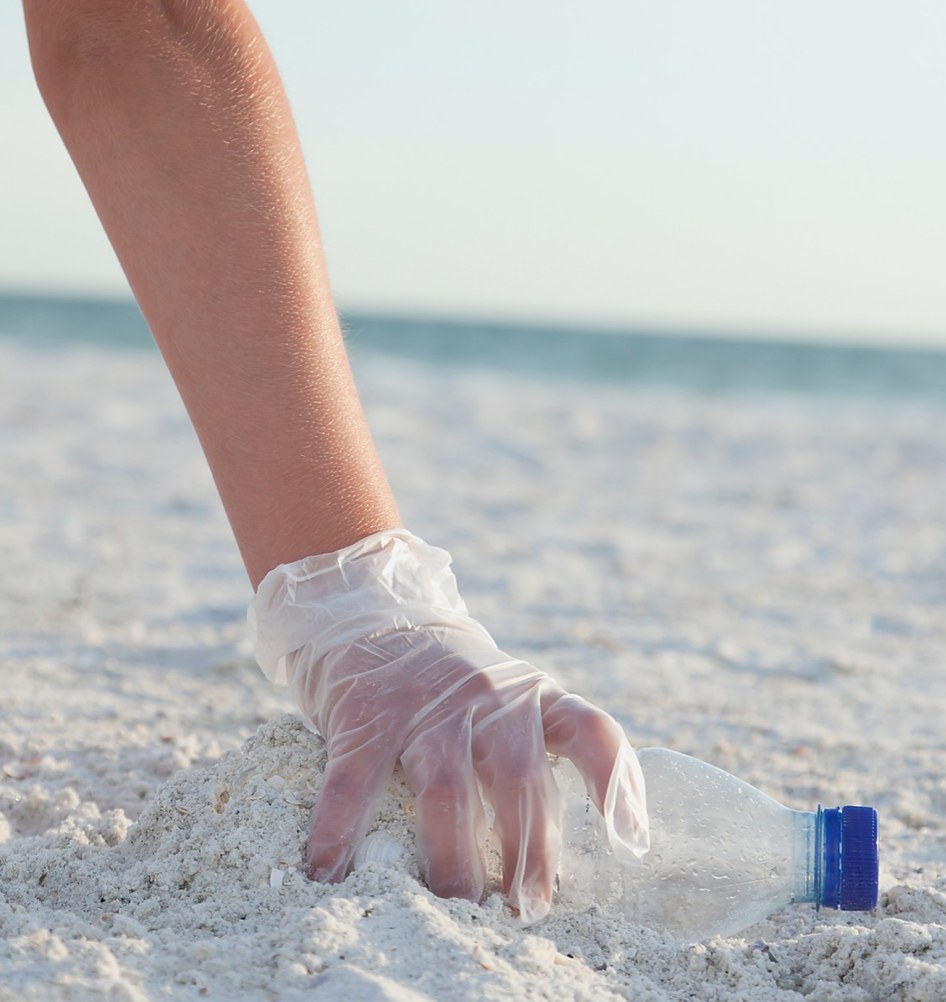 Hand picking up plastic trash at the beach