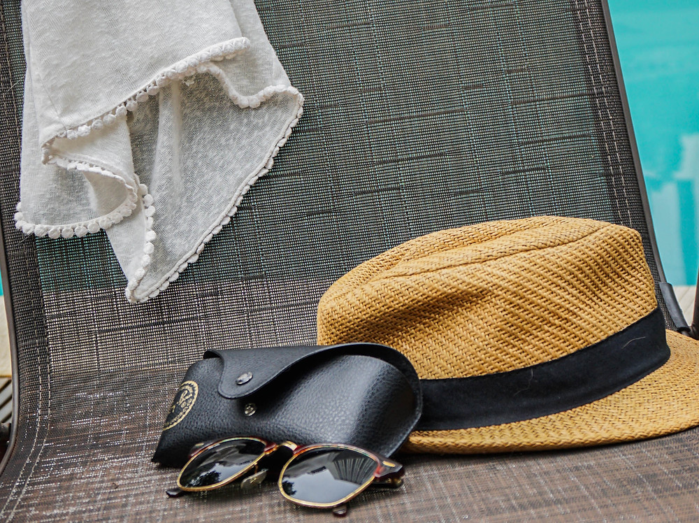 hat and sunglasses on a chair next to a pool