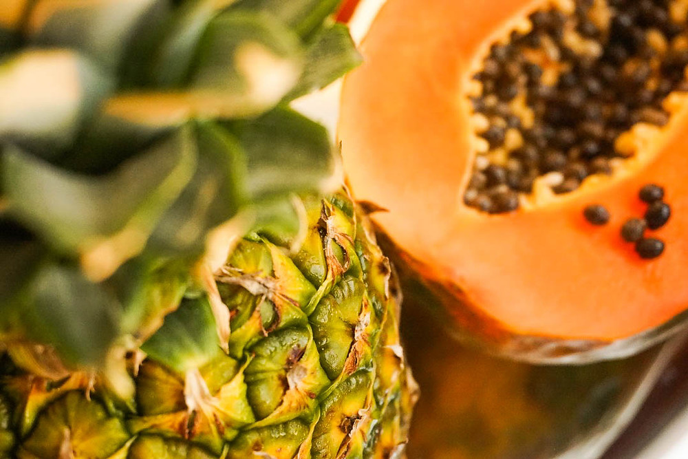 A pineapple and papaya are lying on a table ready to be used in a smoothie.