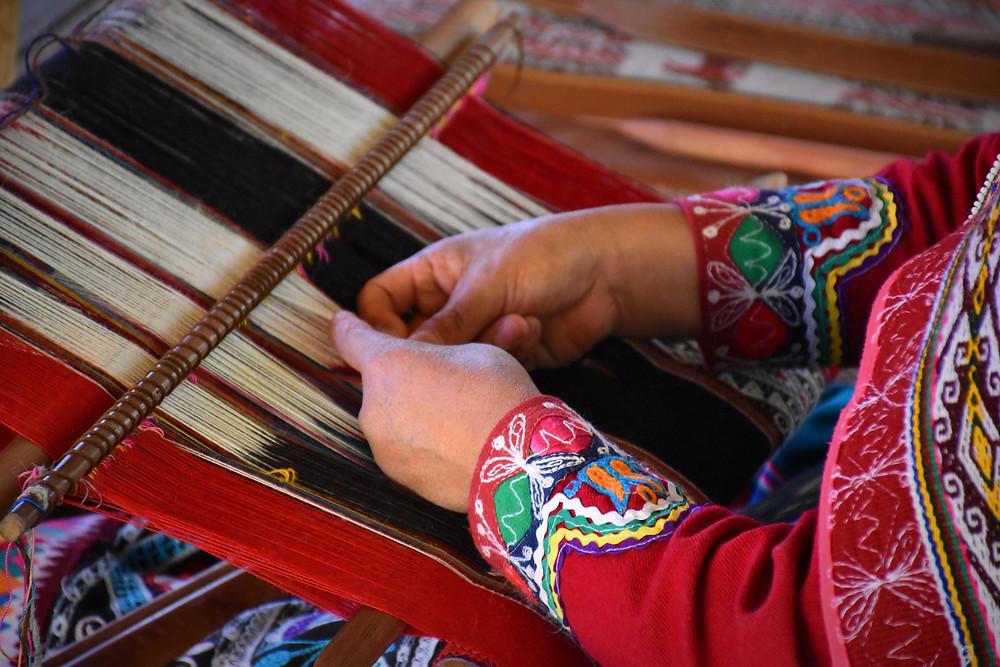 Hands working on Peruvian fabrics