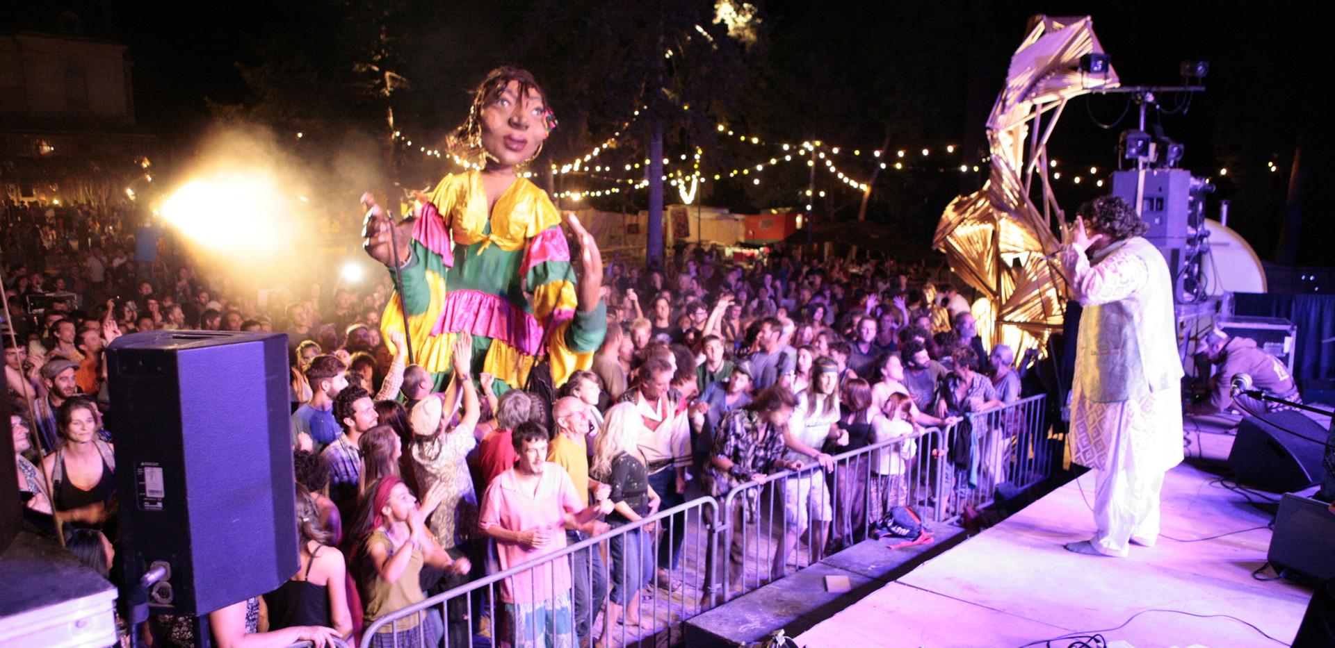 Shahzad, porté par l'énergie du festival, se lève pour faire face au public et aux marionettes géantes