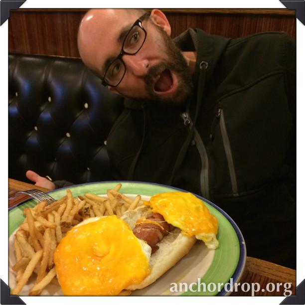 author's husband eating a bacon corndog