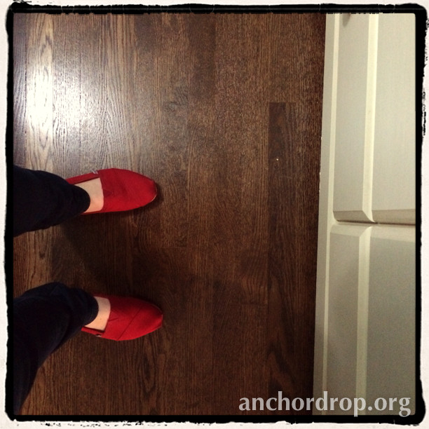 woman's feet wearing red shoes