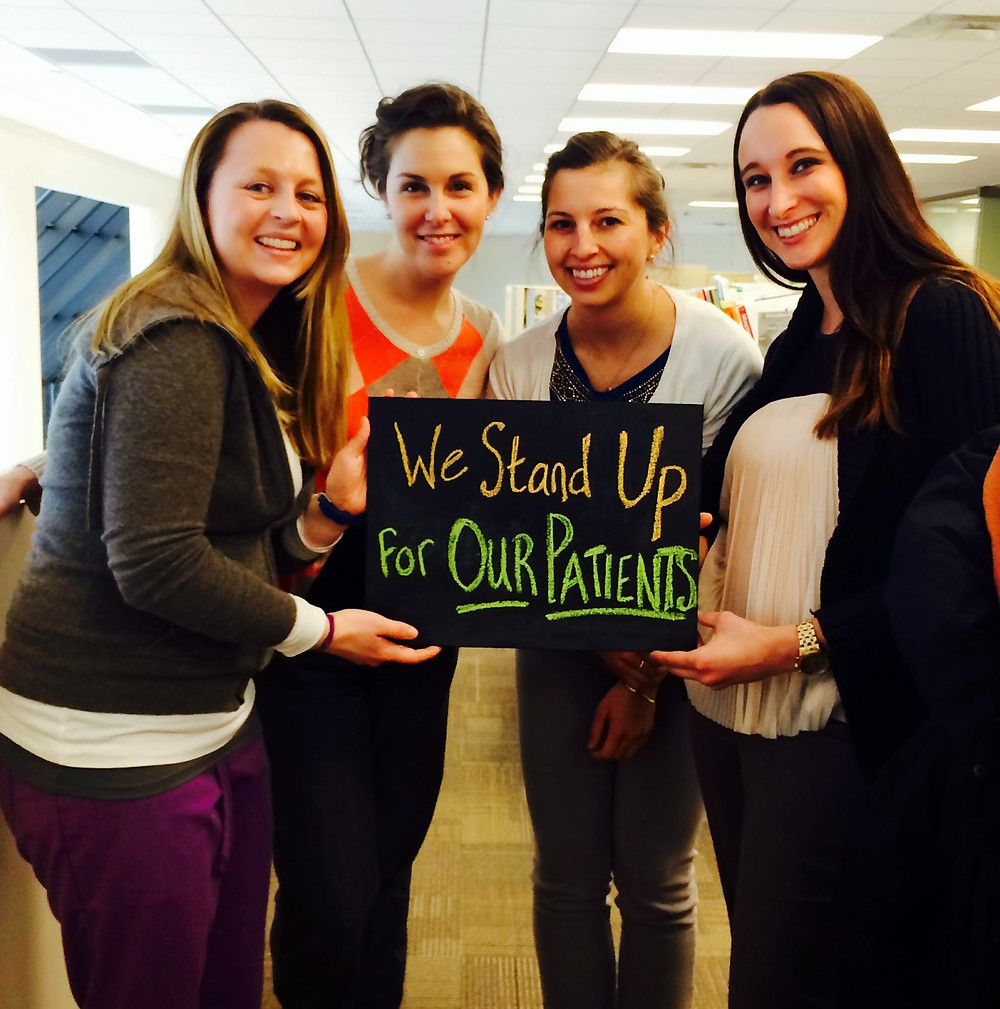 the author and coworkers holding a sign that says we stand up for our patients
