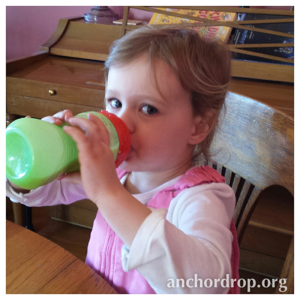 toddler drinking smoothie out of a bottle