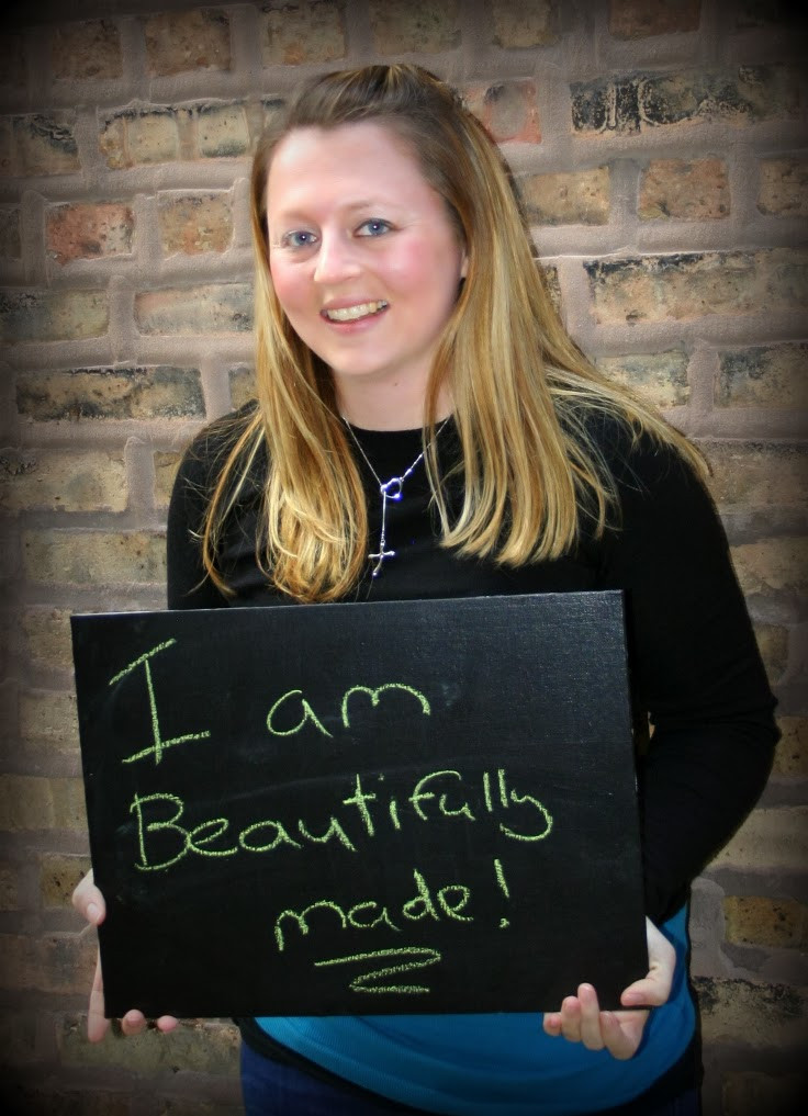 author holding a sign that says I am beautifully made