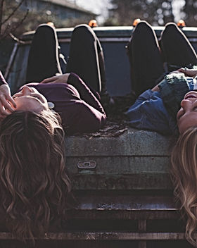 two female friends lying on a truck hood talking