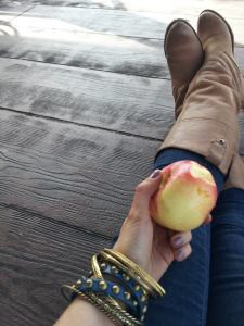 woman in boots holding a bitten apple