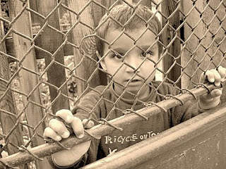 child behind a chain link fence