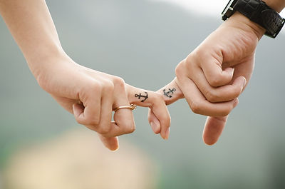 Two people holding each others forefingers which have anchor tattoos
