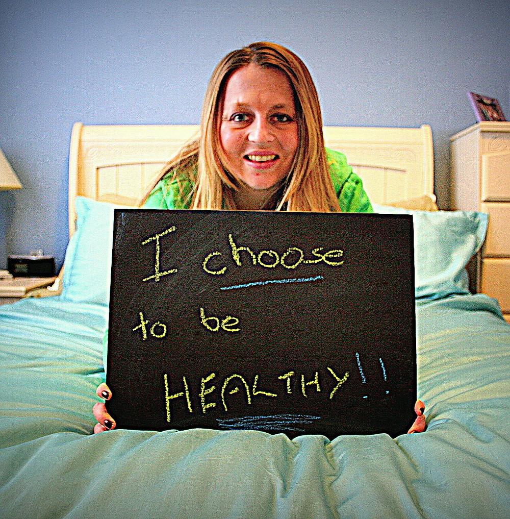 the author holding a sign that says I choose to be healthy