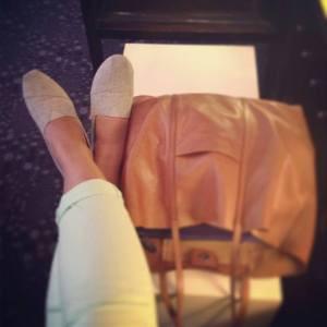 A woman's feet next to a travel bag