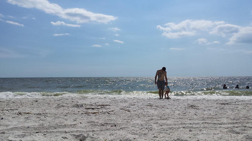 man and young son on the beach