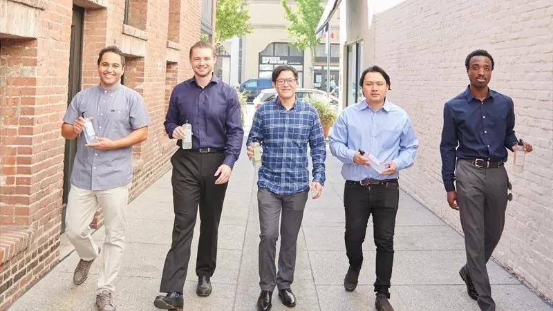 Five men holding sympol hand sanitizer
