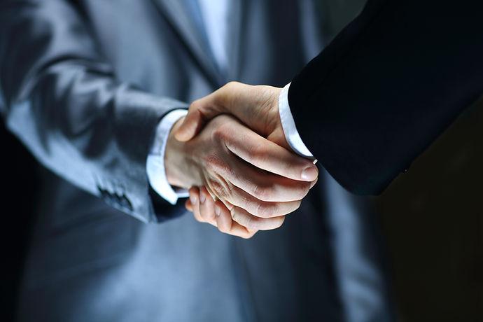 Handshake - Hand holding on black background.jpg