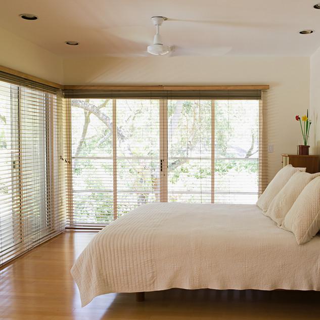 Schlafzimmer mit grossen Fensterfronten und Aussenrollos