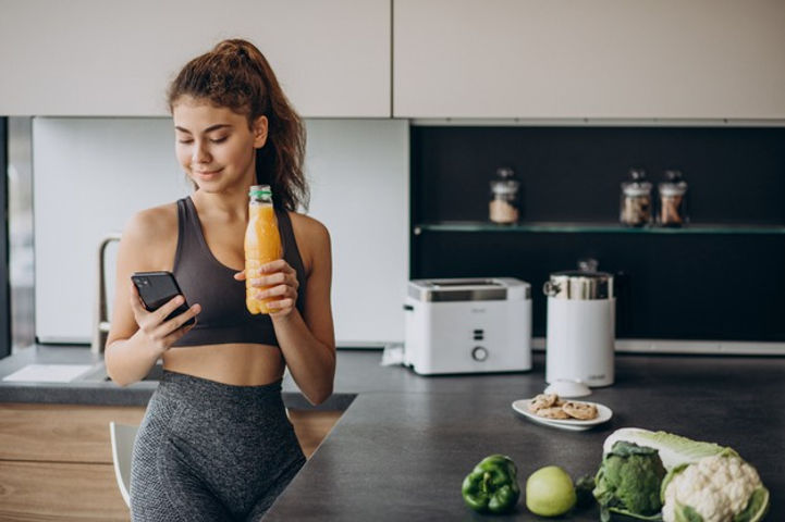 sporty-woman-kitchen-using-mobile-phone_