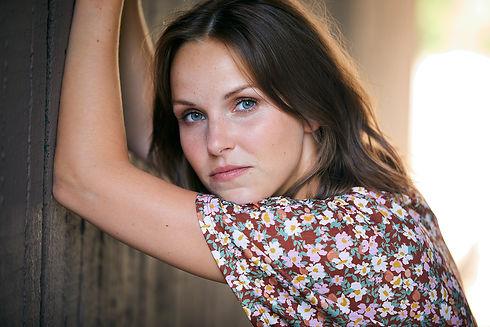 Anika Geyer Frontalbild mit Blumenkleid an einer Wand lehnend