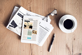 news papers on a table with pen and glasses