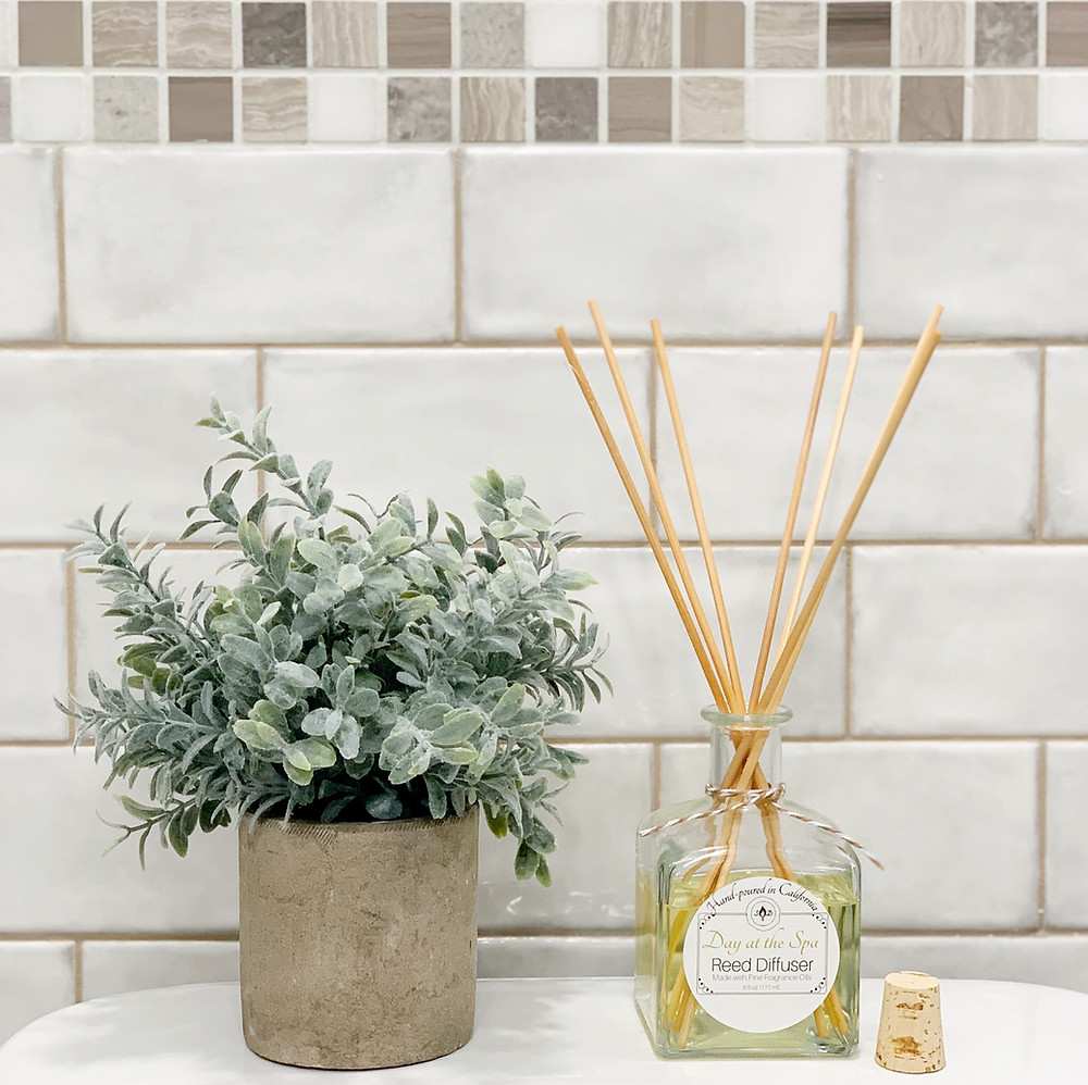 reed oil diffuser in bathroom with plant