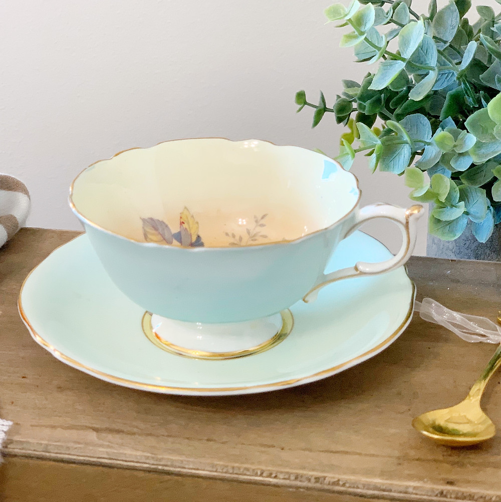 Pale blue teacup with gold teaspoon