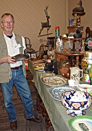 Dealer at Bytown Antique and Bottle Club Show and Sale holding decoy duck.
