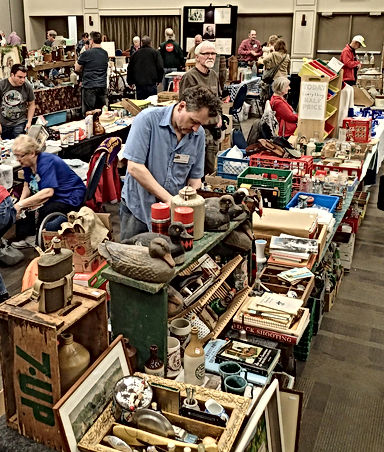 Antique dealer preparing to sell collectibles at the Bytown Antique and Bottle Show and Sale at the Nepean Sportsplex, Ottawa, Ontario.