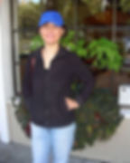 Ja Kim, owner & stylist at Shear Perfection Hair Salon in Berkeley CA wearing blue jeans, black jacket, & blue baseball cap