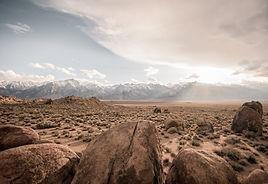 White mountains behind the rocky desert plain