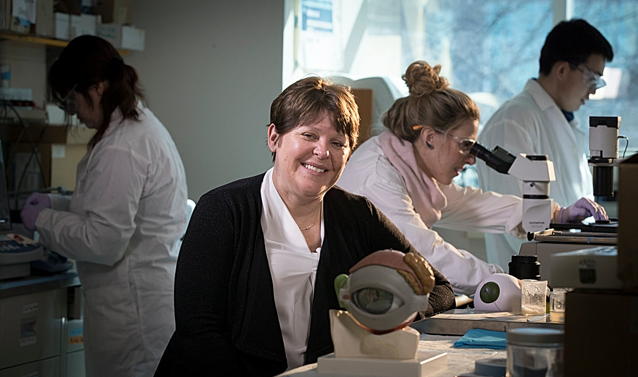 Dr. Heather Sheardown posing in a laboratory with a model of a human eye. Researchers are behind her preparing samples and looking through a microscope.