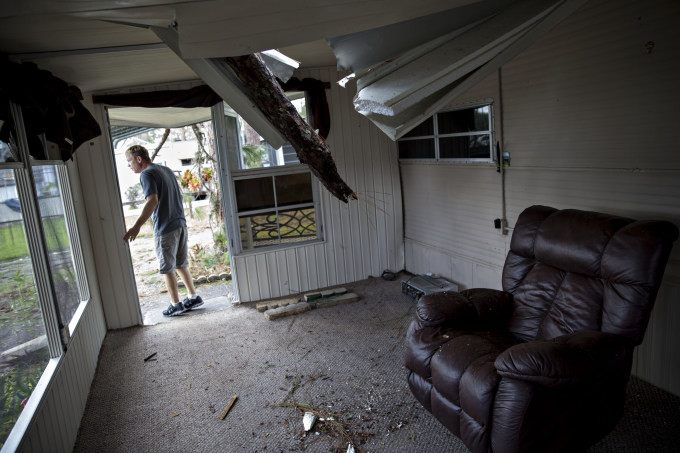 A resident surveys the damage to his trailer after a tree punctured the roof at the Camp Inn RV Park in Frostproof, Florida, during Hurricane Irma. Daniel Acker/Bloomberg