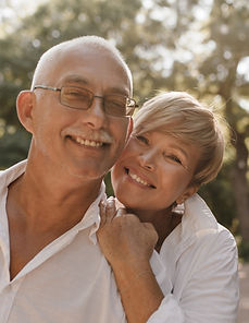smiling-old-man-with-grey-hair-and-mustache-in-glasses-and-light-shirt-hugging-with-blonde