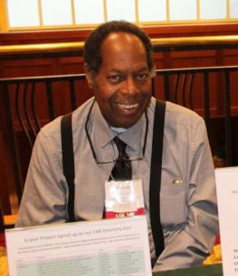Middle-age black man, sitting down, smiling, holding up a laminated paper.