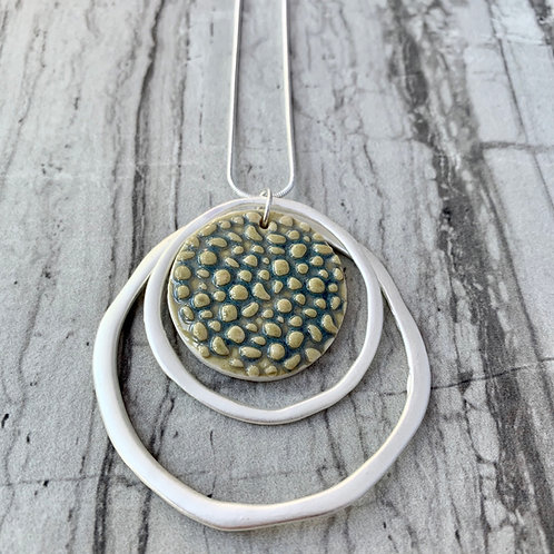 Textured circle in green with silver circles