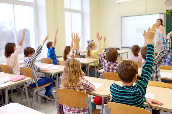 group-of-school-kids-raising-hands-in-classroom-PF36XQ9.jpg