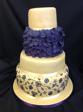 a multi-tier cake with dark blue floral design