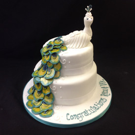 a congratulations cake with a bird on top and its feathers draping down the cake