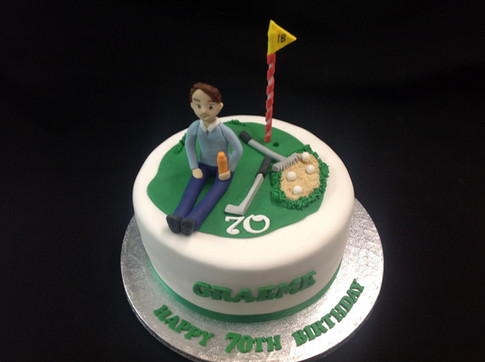 a green and white birthday cake with a golfer sat on a golf green by the hole and flag