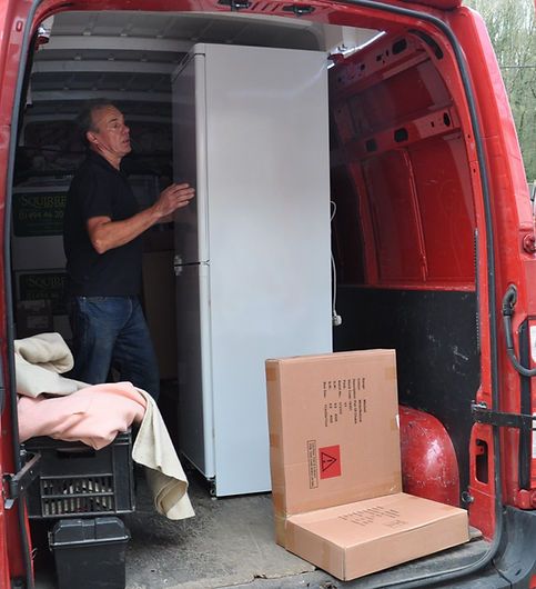 Man holding a fridge steady in a red Renault van
