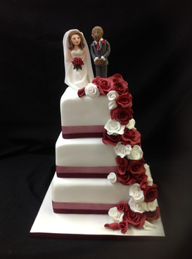 multi tier wedding cake decorated with draping roses and the bride and groom on top