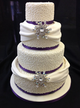 Purple and white multi-tier cake with ribbon and jewel on the front