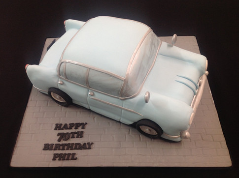 a car birthday cake with happy 70th birthday Phil written on the base
