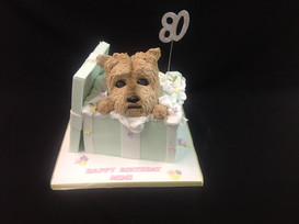80th birthday cake with a small dog in an open gift box