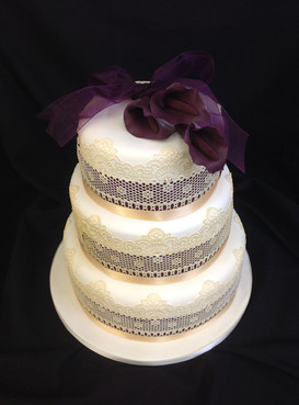 a multi-tier cake with decorative pattern around the edges and purple flowers on top