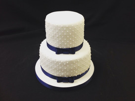 2 tier cake with stud decoration and purple ribbon