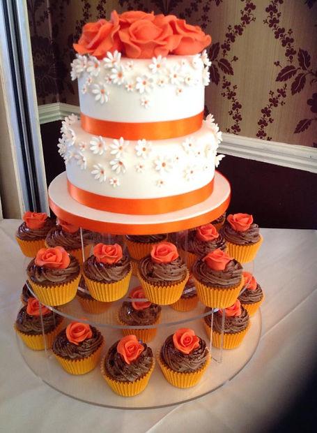 an orange and white multi tier cake with cupcakes around the bottom