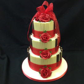 3 tier cake decorated with red ribbon and roses