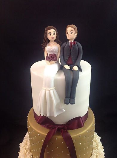 gold and white studded cake with red ribbon and the bride and groom sat on top